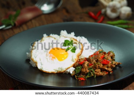 Thai food, Pad Ka Phrao, fried meat with chili, garlic and holy basil. eat with rice and fried egg. - stock photo