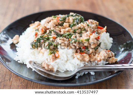 Thai food, rice topped with stir-fried pork and basil.