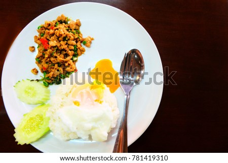 Thai Food Rice Topped with Stir-Fried Pork and Basil with Fried Egg in White Dish Background Great for Any Use.