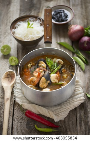 Thai food spicy and sour tom yam soup with seafood in cooking pot, served with rice noodle on rustic wooden table top.  - stock photo