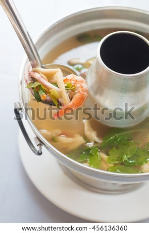 thai food, spicy seafood soup in hot pot. - stock photo