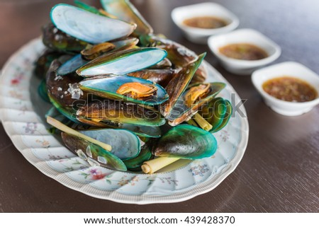 Thai Food, steamed mussels with basil and lemongrass. Eaten with spicy sauce. - stock photo
