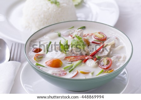 Thai Food, Tom Kha Gai, chicken soup in coconut cream in white with steamed rice beside.