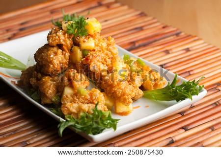 Thai fried calamari appetizer garnished with fresh pineapple chunks. - stock photo