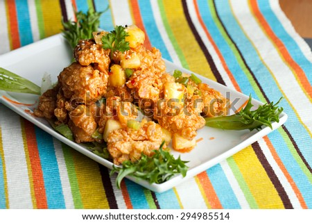 Thai fried calamari appetizer garnished with fresh pineapple chunks. - stock photo