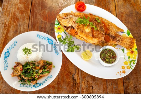 Thai fried fish and cooked on a plate with lemon and the peel of an tomato - stock photo