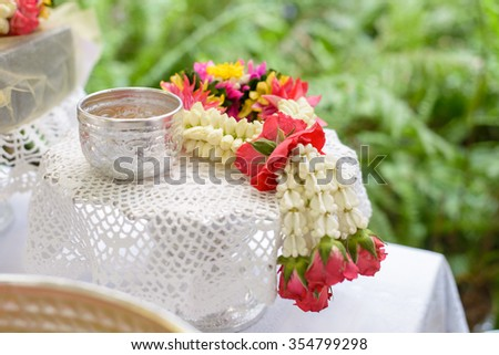 Thai garland Flowers and Water with jasmine and roses corolla in bowl on golden tray (Use for Songkran festival in Thailand) - stock photo