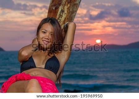 Thai girl with long tailed boat on the beach - stock photo