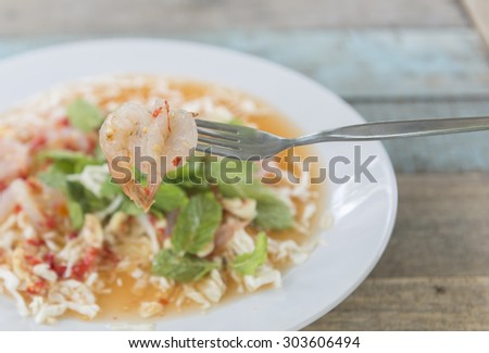 Thai gourmet rustic dishes -Fresh shrimps in sauce and spicy salad dip in the fork.  - stock photo