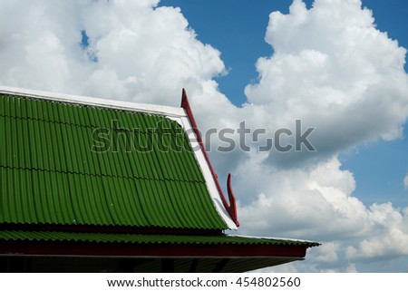 Thai hand crafted wooden roof of Thai house under blue sky with clouds