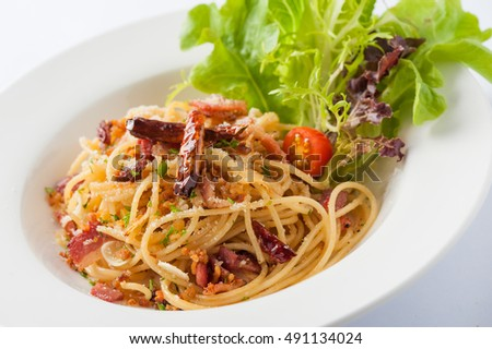 Thai, Japanese, and European fusion food style spicy pasta with bacon and dried chili in ceramic dish