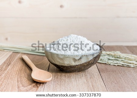 Thai jasmine rice in ceramic cup  and wooden spoon - soft focus - stock photo