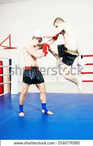 Thai kickboxing. Muay thai boxers fighting at training boxing ring - stock photo