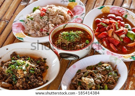 Thai launch/dinner set,  curry, pork, spicy salad and sticky rice, on bamboo background - stock photo