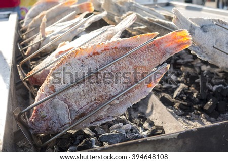 thai local food - fresh delicious Salt Crusted Grilled Fish in street market, bangkok, thailand - stock photo