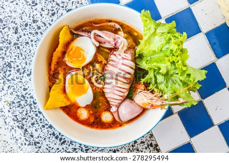 Thai local food: Noodles seafood spicy is Hot noodles add squid, shrimp, egg and meat ball. - stock photo
