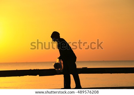 Thai man beach sweeper cleaning working keep garbage and push garbage cart at the road on sunrise background