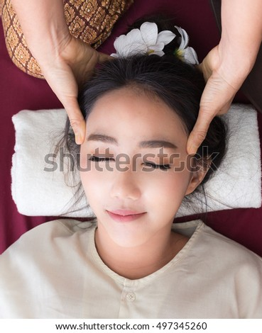 Thai massagist doing massage for woman in spa salon