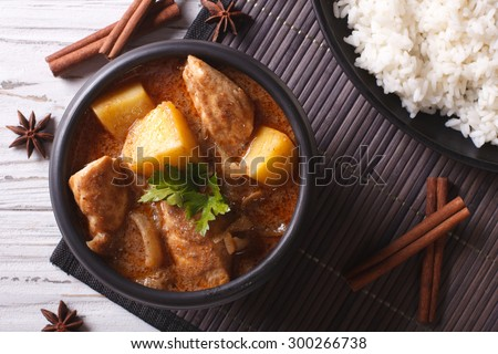 Thai massaman curry with chicken in a bowl and rice on the table close-up. horizontal top view - stock photo
