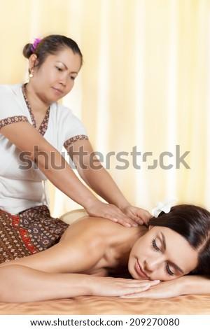 Thai masseur doing massage for european woman in spa salon - stock photo