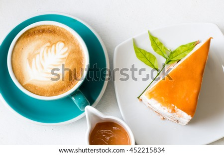 Thai milk tea Crepe cake , served with a cup of latte art coffee - stock photo