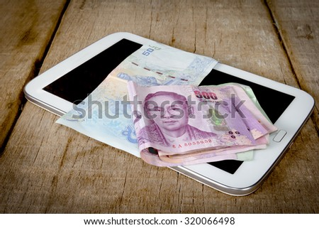 Thai money banknotes on tablet computer - stock photo