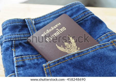 Thai Passport in the pocket jeans Preparation for travel Vacations,(Thai language on passport book is Thailand Passport), blurred