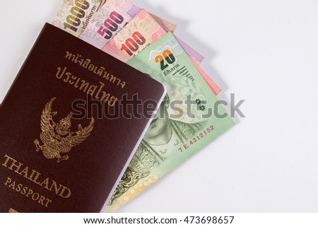 Thai Passport with Thai money banknote isolated on white. The passport of Thai citizen on Thai banknote.