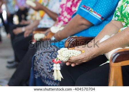 Thai people celebrate Songkran new year water festival 13 April by giving garlands to their seniors and asked for blessings - stock photo