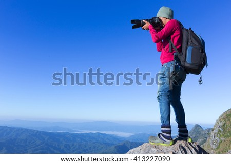 Thai photographer or traveller using a professional DSLR camera in the nature for background - stock photo