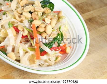 Thai Rice Noodle Salad in a bowl sitting on a wooden table. - stock photo