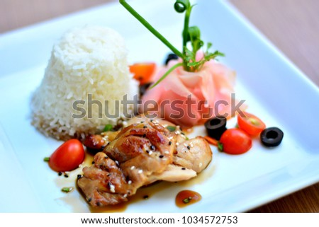 Thai roasted chicken, Black sesame and tomato wite rice in white plate on wood table, thai food