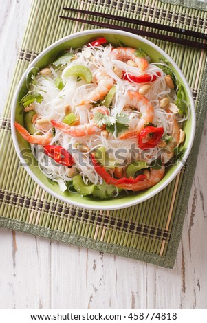 Thai salad with glass noodles, prawns and peanuts in a bowl close-up. vertical view from above - stock photo