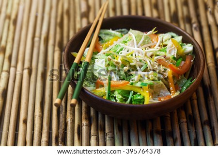 Thai salad with greens, vegetables and sprouts on a bamboo table - stock photo