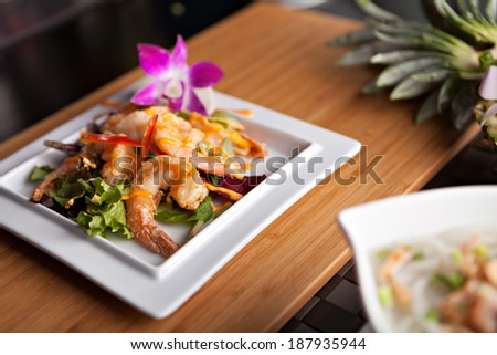 Thai shrimp dish presented on a white square dish.  Shallow depth of field. - stock photo