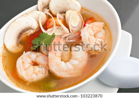 Thai shrimp soup bowl close up with mushrooms and vegetables.