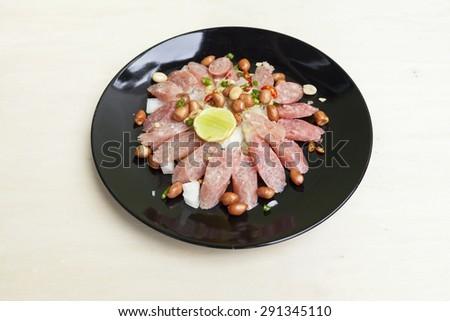 Thai sour pork sausage salad in black plate  - stock photo