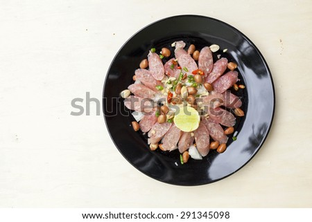Thai sour pork sausage salad in black plate with space on wood background - stock photo