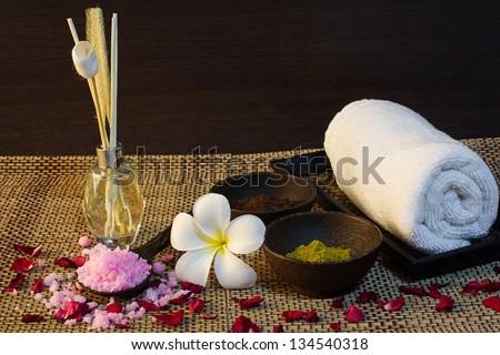 thai spa aroma setting  with aroma reed diffuser, spa mud, bath salt on spoon, frangipani, towel and rose patals - stock photo