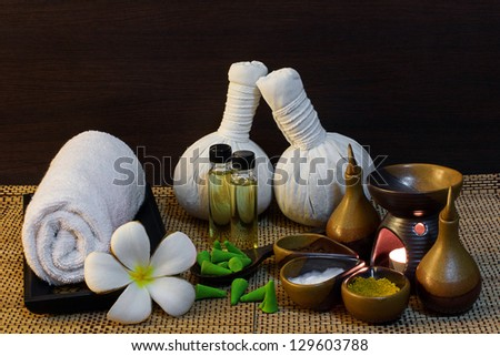 Thai spa massage setting with spa mud,  herbal compress balls, essential oil bottle, towel, frangipani and incense cone - stock photo