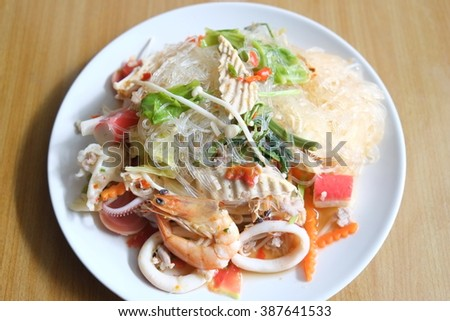 Thai spicy glass noodle salad with seafood on the plate. (yam vun sen)