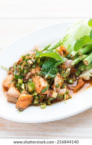 Thai spicy minced Salmon with salad on wood table - stock photo