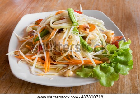 Thai spicy shrimp papaya salad on white dish with natural lighting from the right