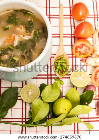 Thai spicy Tom Yam Koong in pot with ingredients - stock photo