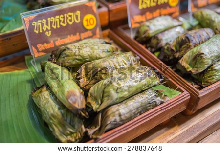 Thai style banana leaf wrapped food, made from sticky rice, pork and peanut - stock photo