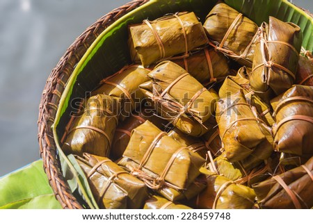 Thai style dessert, made from banana and glutinous rice, wrap with banana leaf - stock photo