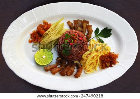 Thai style food. Shrimp paste fried rice . Famous  native Thai food fried rice with shrimp paste and compound with sour mango , sweet pork ,thin sheet egg, spicy with chili. - stock photo