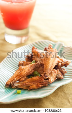 Thai style fried chicken wings on green table with red cold drink