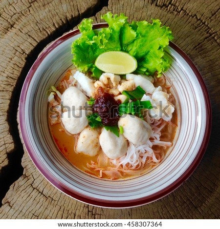Thai style noodle, Chinese clear soup in traditional ceramic bowl on wooden table. - stock photo