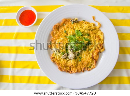 Thai style oyster omelet with sauce, fried beaten egg with parsley on top - stock photo